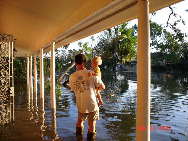 FLOOD CAME AFTER STORM: Rudy Horvath holds his son, Rudy Jr., and surveys his yard / Photo: Dawn Ricks Horvath